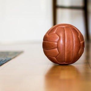 Handgenähter Fußball aus Leder in der Farbe Natur. Liegt auf dem spiegelnden Holzboden.